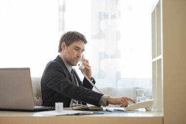 real estate agent dialing telephone number sitting at his office desk