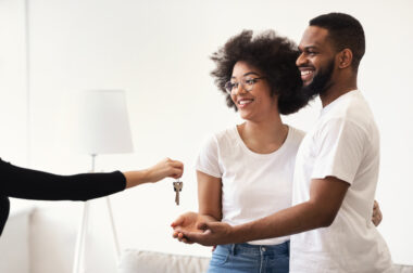 Real Estate Agent Giving House Key To Black Couple Indoors