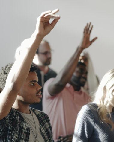 People raising their hands in a seminar